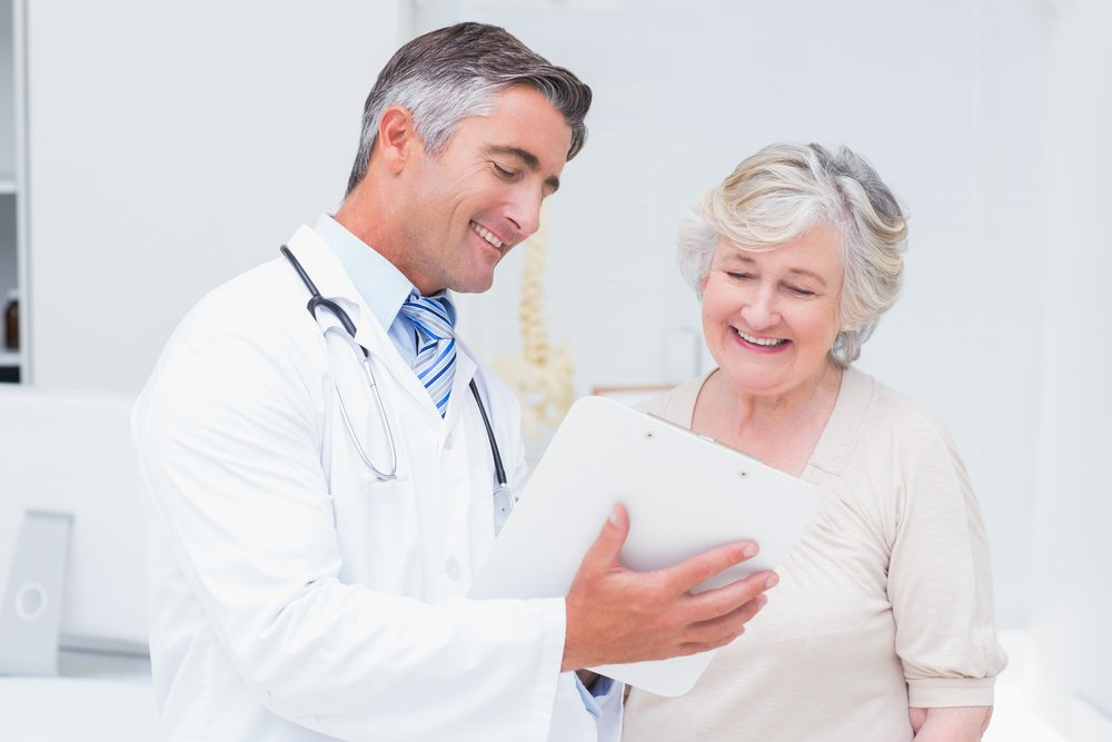 Happy doctor and patient discussing over reports in a clinic | Photo: Shutterstock