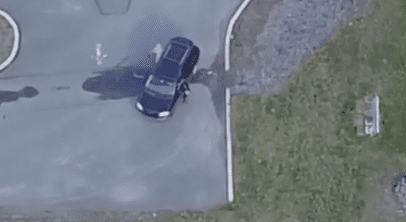 Drone footage of the wife greeting another person before getting into their car. | Photo: Metro