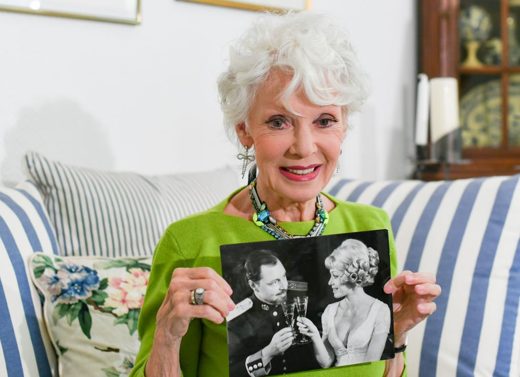 """06 May 2020, Berlin: EXCLUSIVE - The actress Anita Kupsch shows a photo in her apartment, which she showed in the 1960s in the play """"The Prince and the Dancer"""" at the Hebbel Theatre with actor Ivan Desny. She celebrates her 80th birthday on 18 May. Photo: Jens Kalaene/dpa-Zentralbild/ZB. 