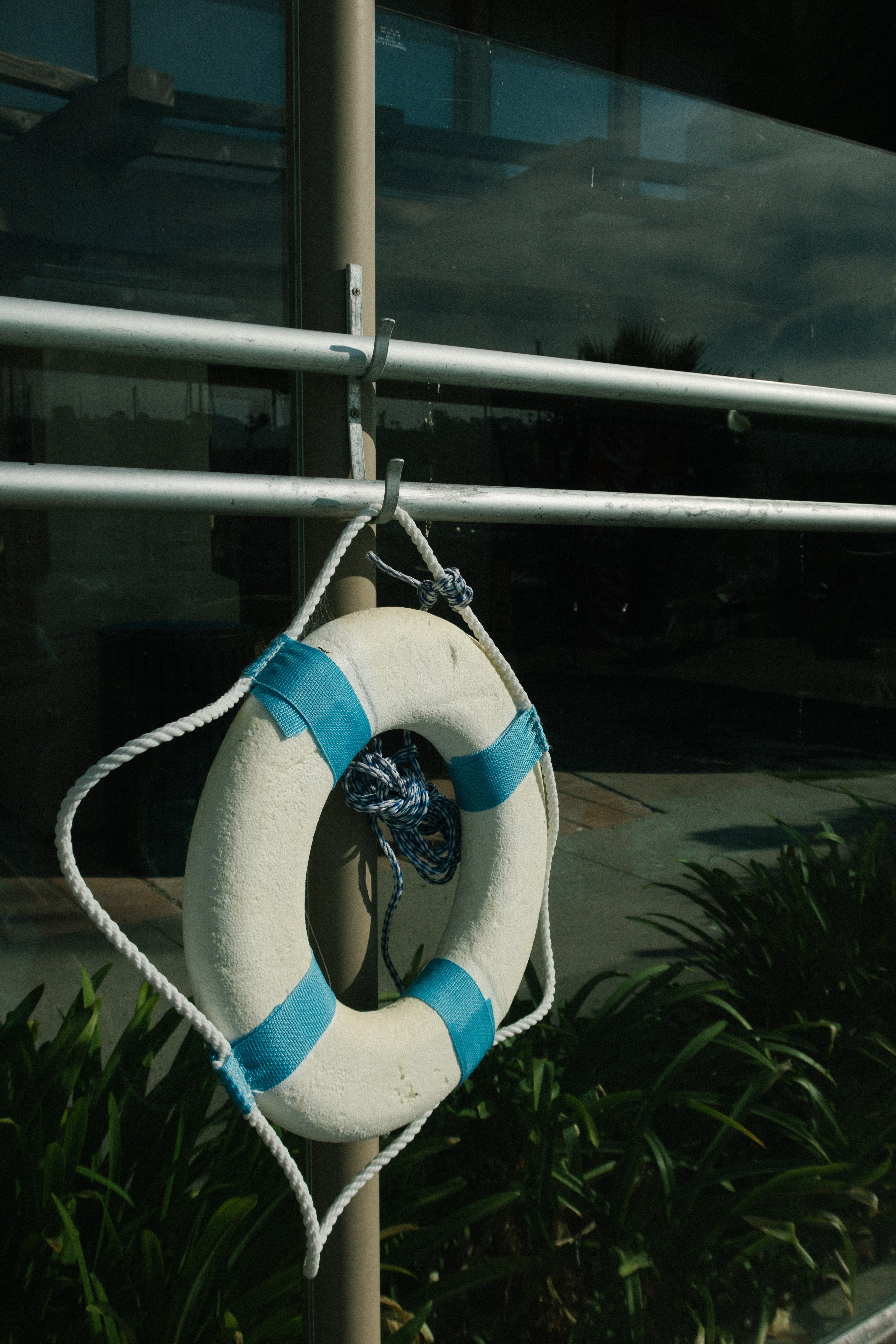 Blue and white life saver buoy attached to a pole.   Pexels/ Athena