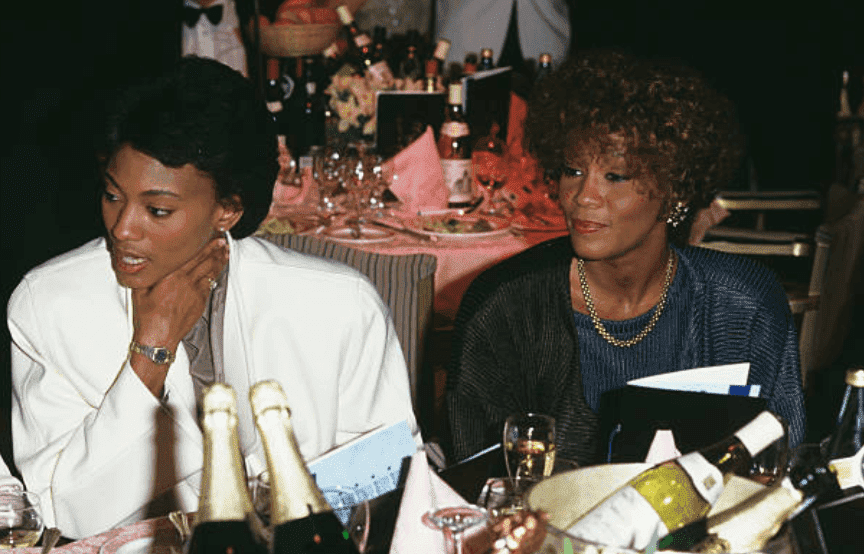 Robyn Crawford Whitney Houston dine at an event with tables decked out with champagne bottles, on January 01 1988 | Source: Dave Hogan/Getty Images