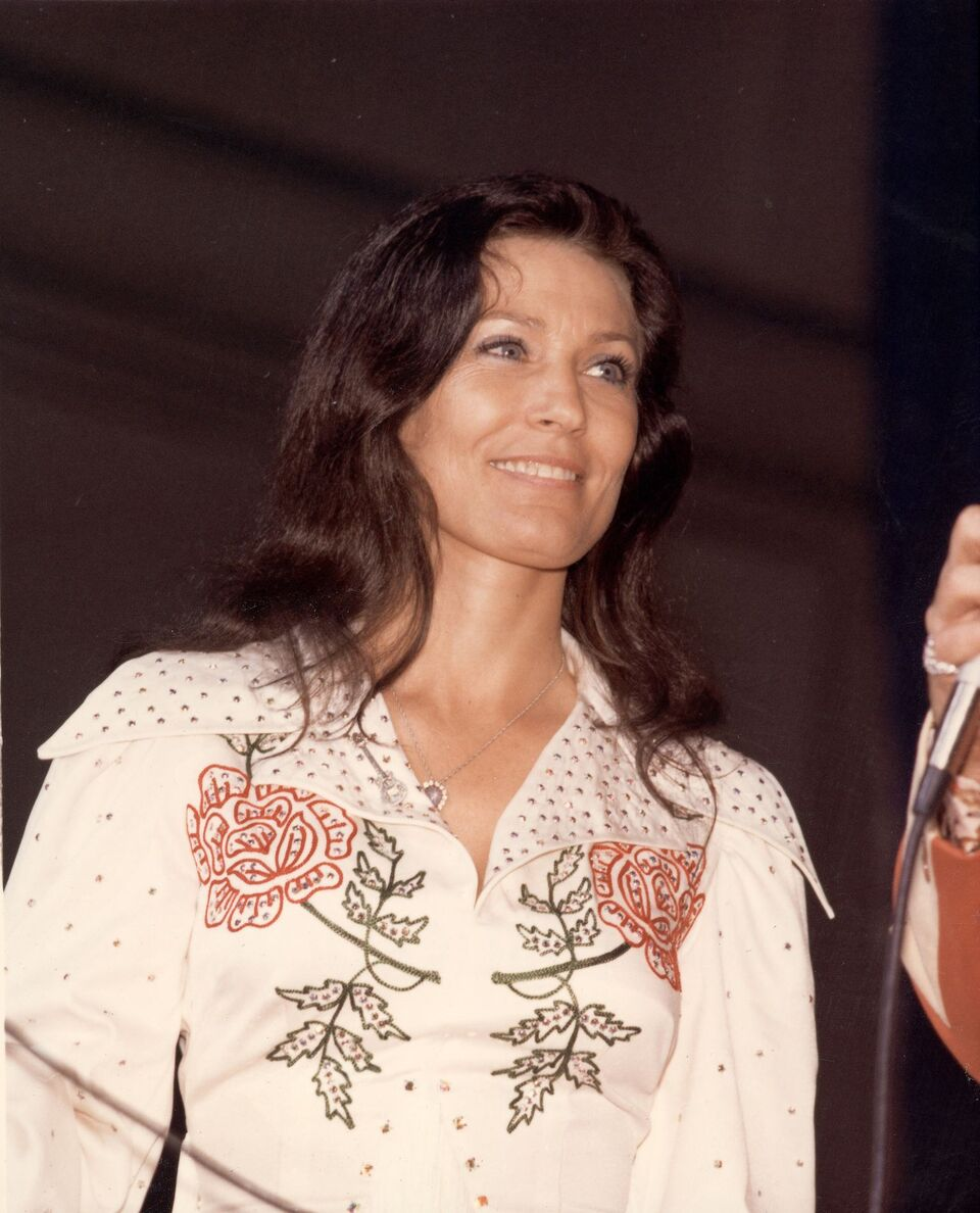 Loretta Lynn smiles as she looks at an unidentified person off-camera who holds a microphone, late 1970s.   Source: Getty Images