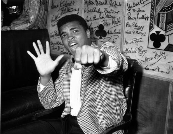 Supremely confident American boxer Cassius Clay holds up five fingers in a prediction of how many rounds it will take him to knock out British boxer Henry Cooper | Source: Getty Images