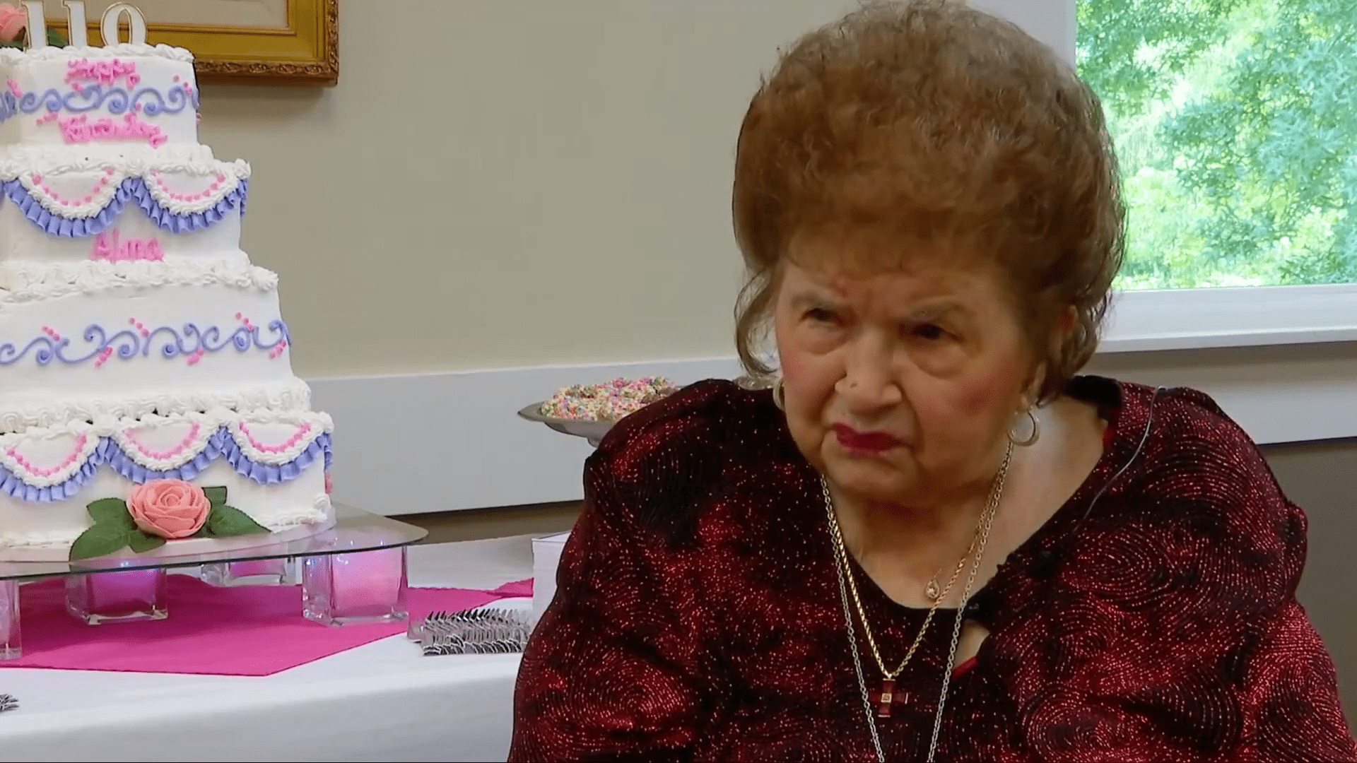 110-year-old Alma Kahl dressed in red and sitting next to her birthday cake.   Source: WOWK 13 News