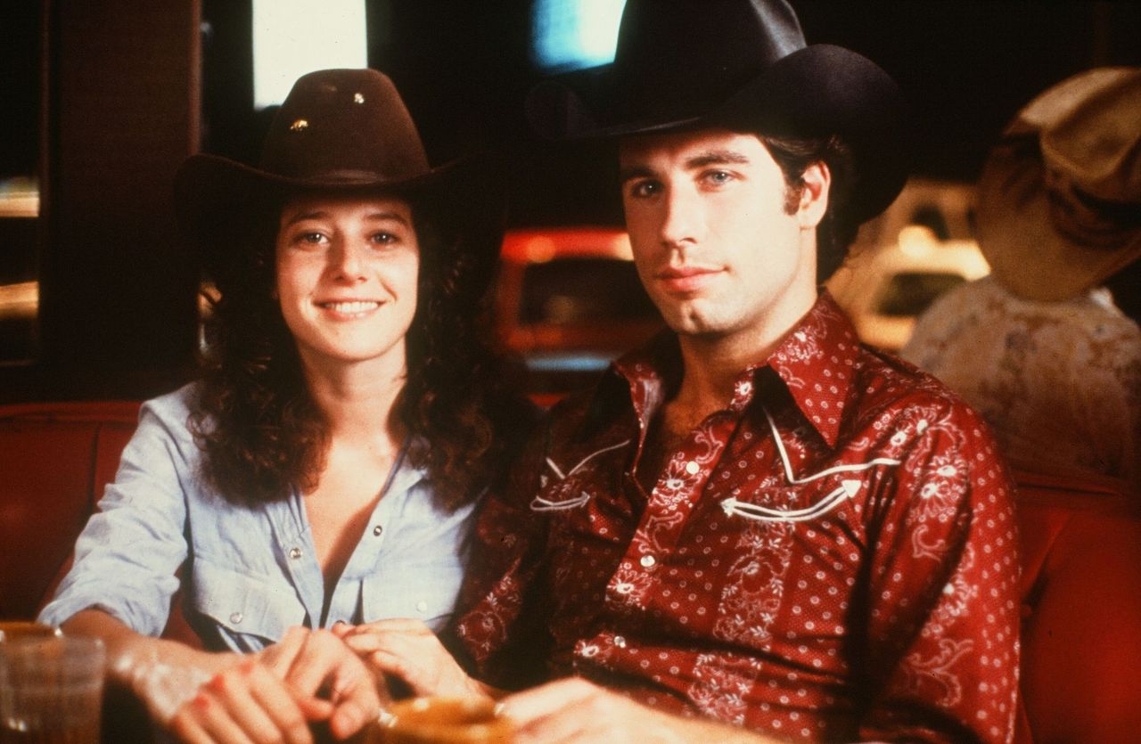 """John Travolta and Debra Winger smile on set of the Paramount Pictures movie 'Urban Cowboy"""" circa 1980. 
