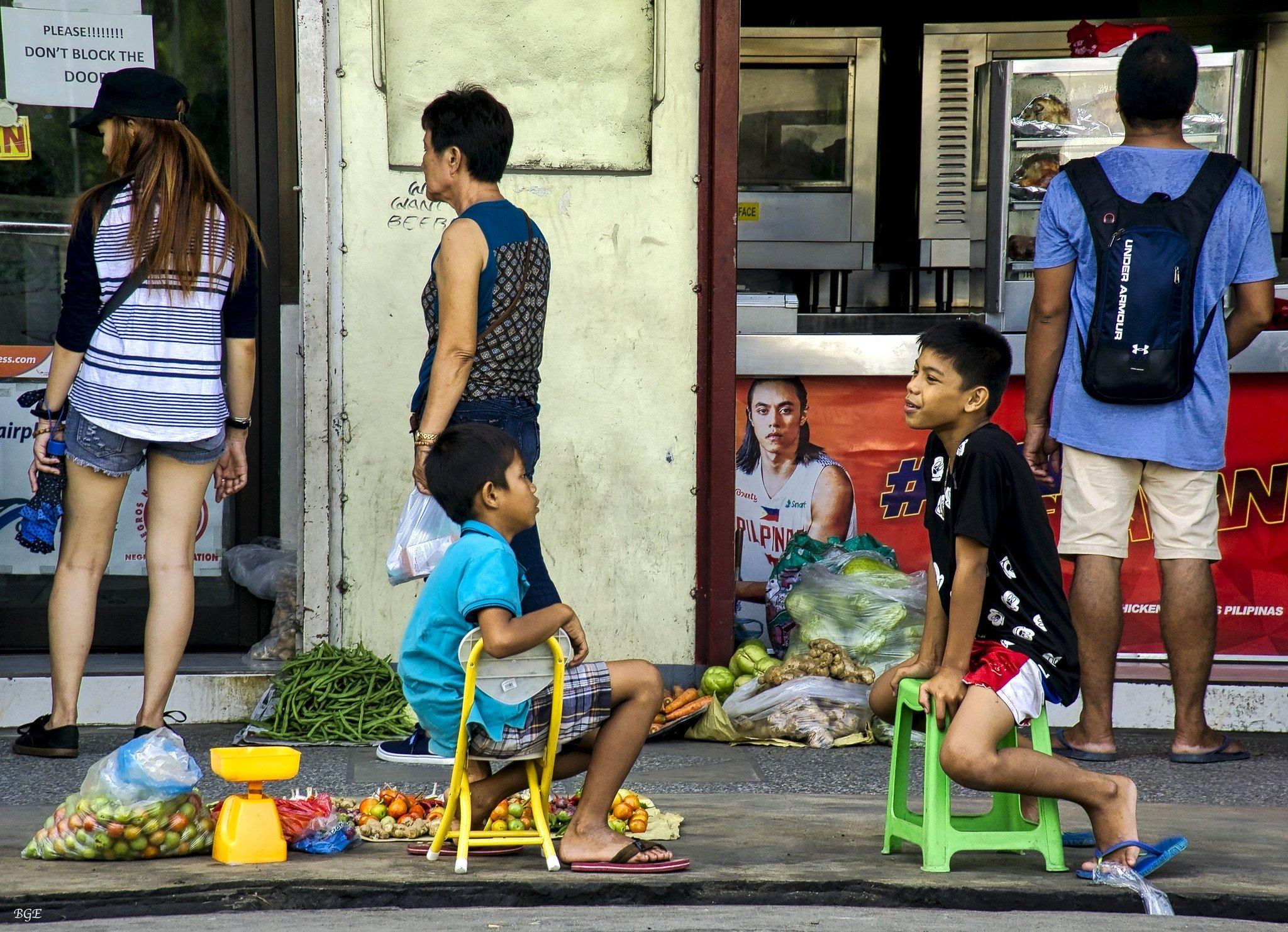 Niños conversando mientras muestran vegetales en una acera. | Imagen: Flickr