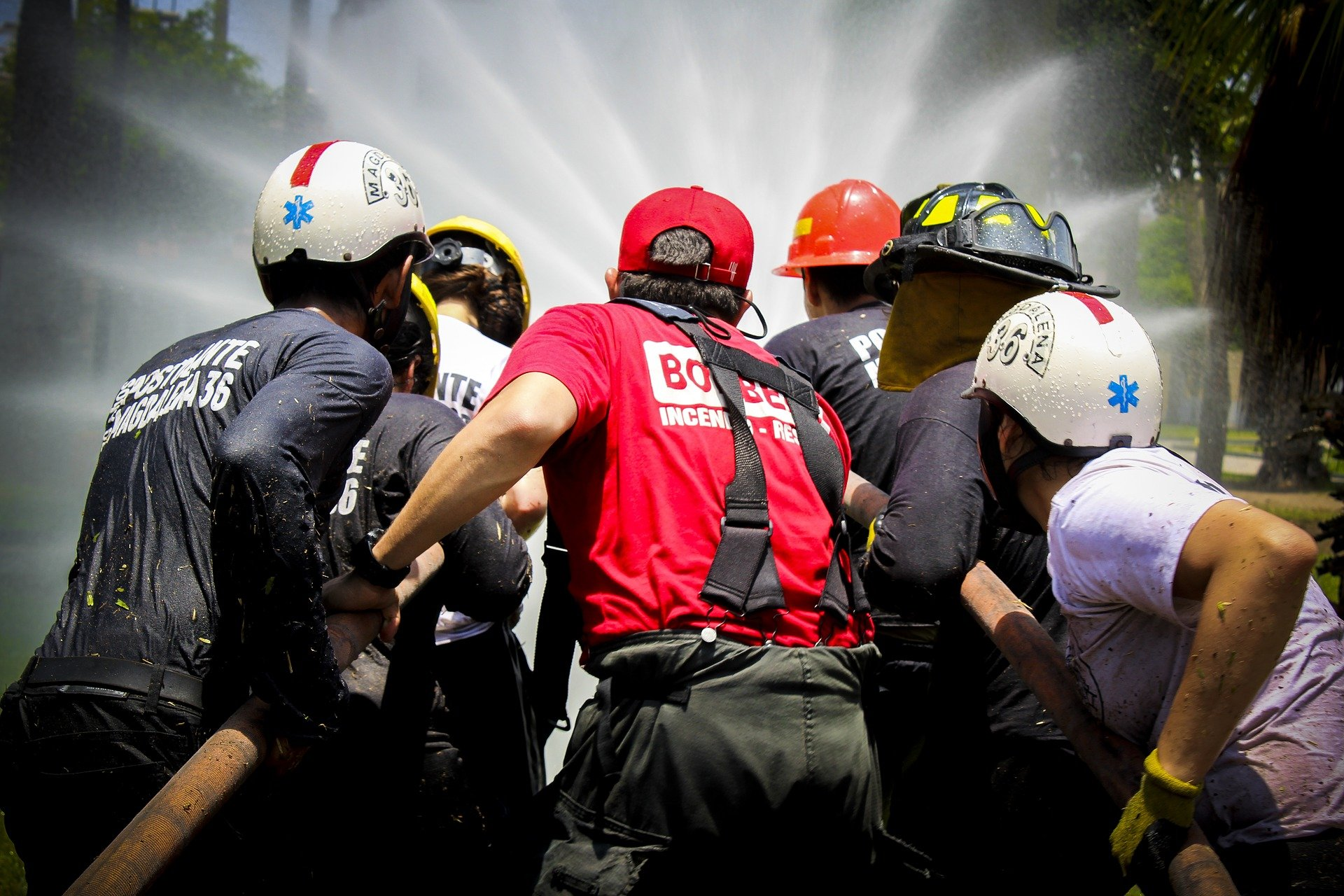 Pictured - An image of fire and water rescue teams wearing helmets and pulling a hose | Source: Pixabay