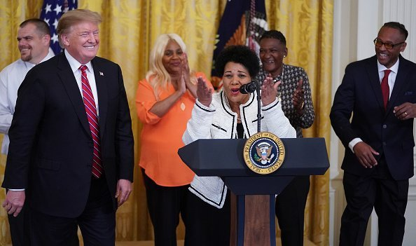 Alice Marie Johnson, who had her sentence commuted by U.S. President Donald Trump (L) after serving 21 years in prison for cocaine trafficking, thanks the press during a celebration of the First Step Act in the East Room of the White House April 01, 2019, in Washington, DC. | Source: Getty Images.