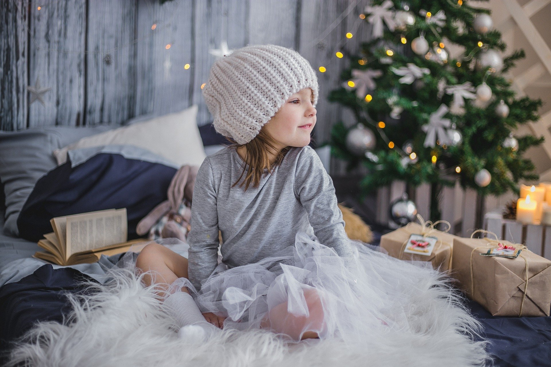 A girl surrounded by presents on Christmas morning.   Source: Pixabay.
