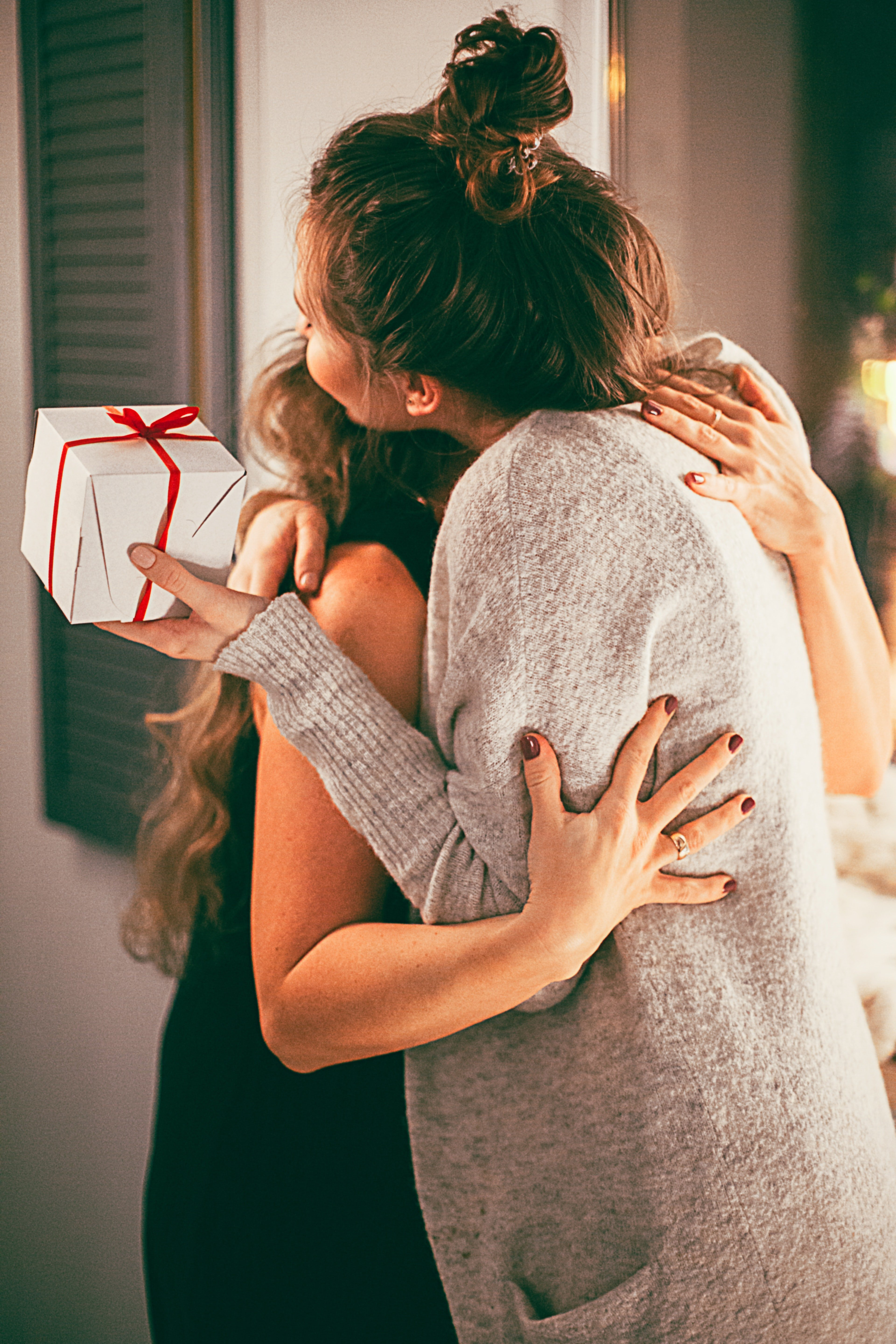 Two women embracing each other with gifts. | Source: Pixabay