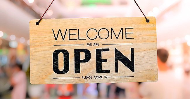 An open sign in front of the door of a store | Photo: Shutterstock