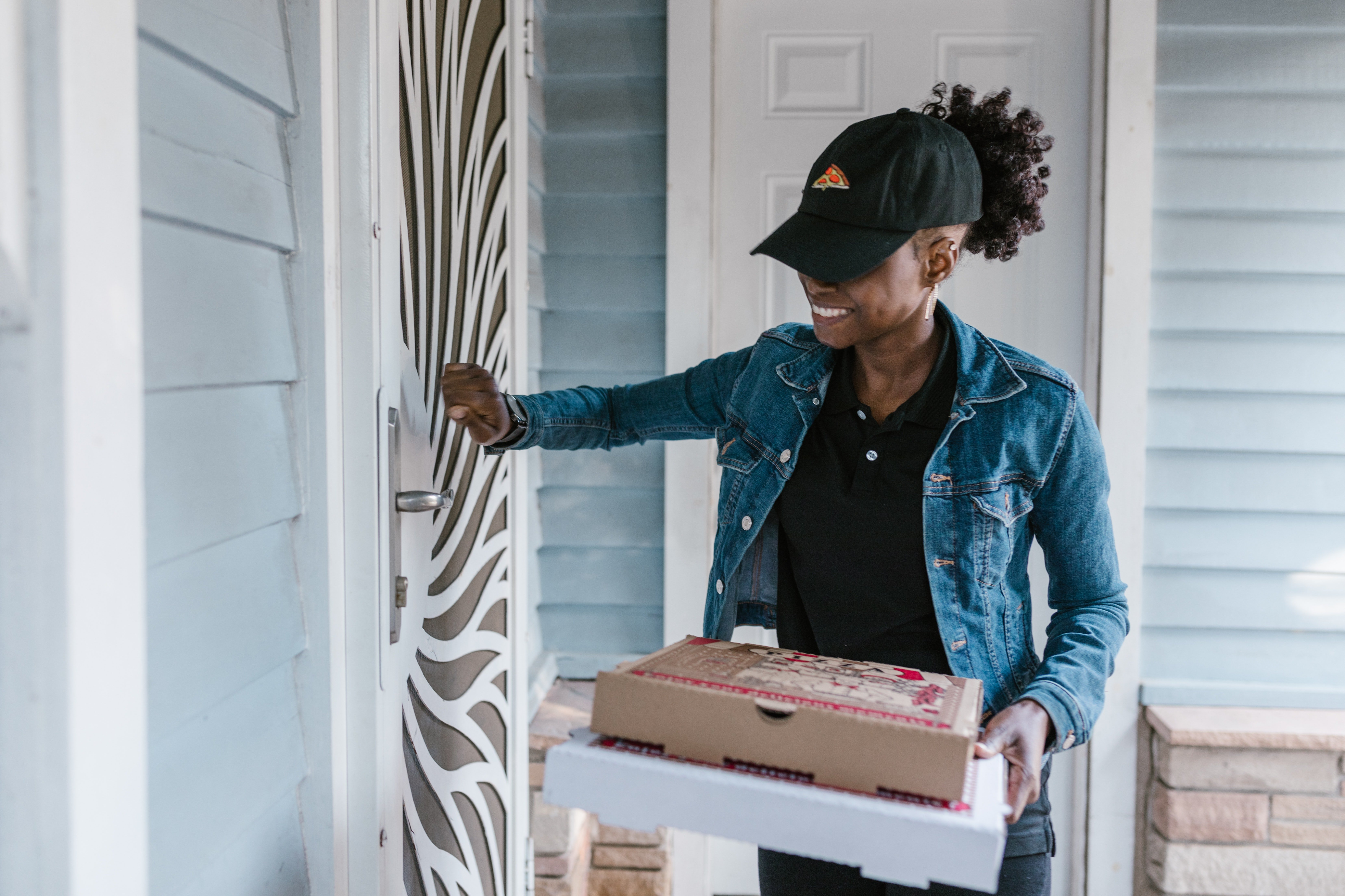 A delivery woman knocking on the door. | Photo: Pexels/RODNAE Productions