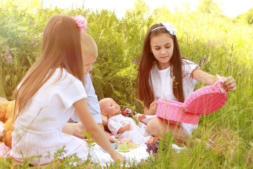 Girls playing with their dolls outdoors. | Source: Shutterstock.