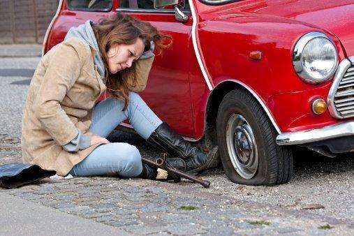 Mujer con un neumático desinflado. | Foto: Getty Images