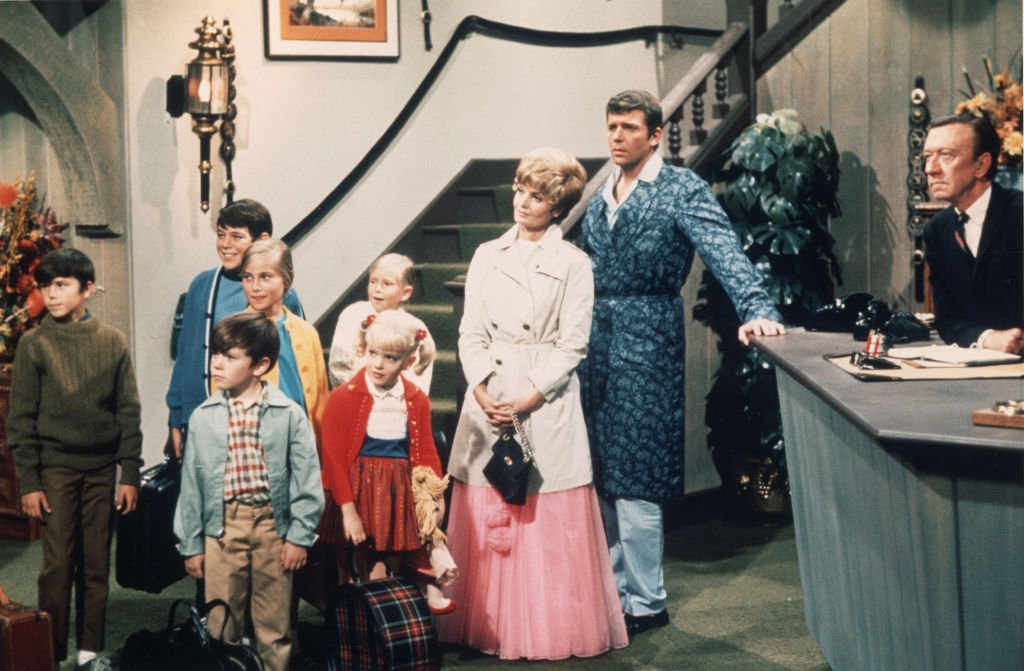 American actors Robert Reed and Florence Henderson stand in a hotel lobby with their television family in a still from the TV series 'The Brady Bunch,' circa 1969. (L-R) Christopher Knight, Barry Williams, Mike Lookinland, Maureen McCormick, Eve Plumb, Susan Olsen, Henderson, Reed | Photo: Getty Images