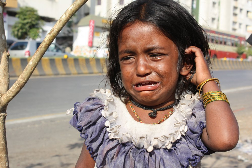 Beggar girl from India crying on the streetside. | Source: Shutterstock