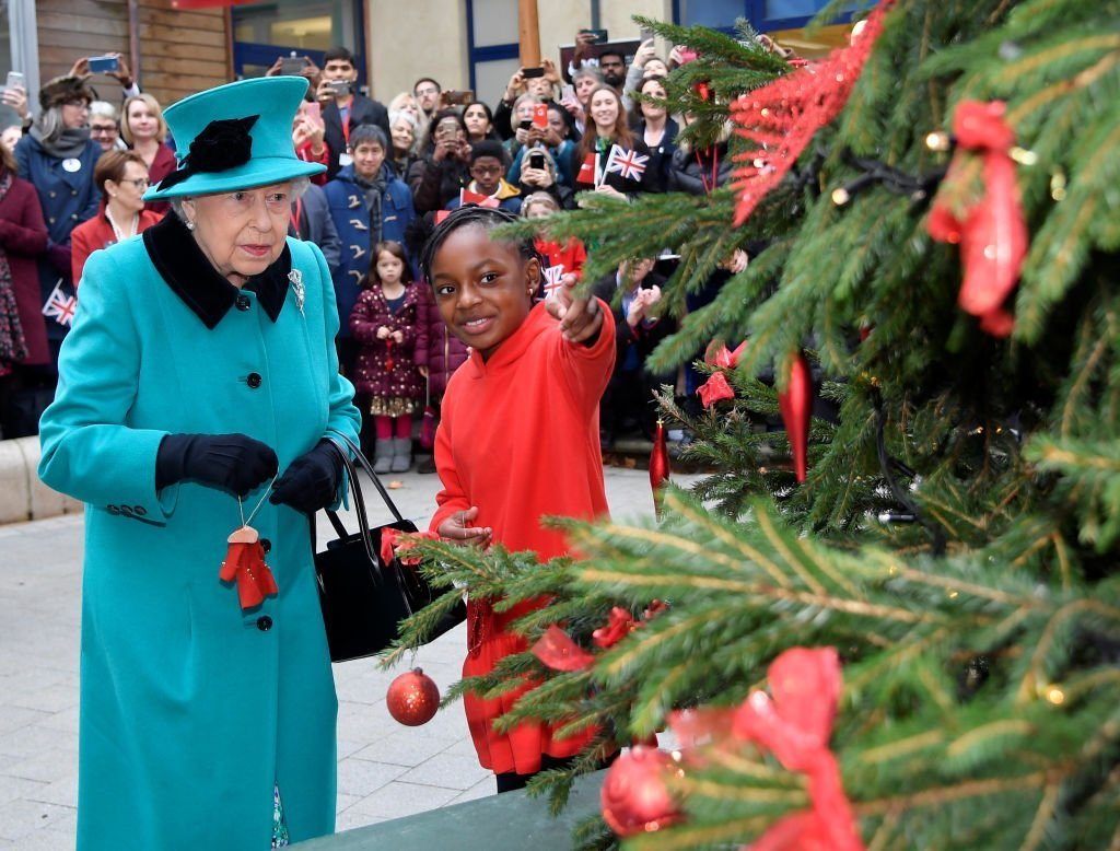 Queen Elizabeth II and Shylah Gordon, aged 8, attach a bauble to a Christmas tree during the opening of the Queen Elizabeth II. | Source: Getty Images