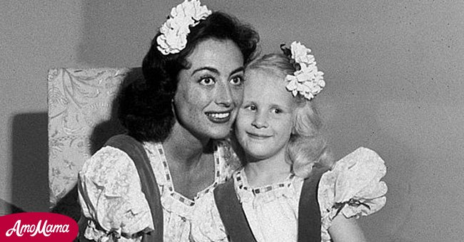 Joan Crawford sits and holds hands with her adopted daughter Christina at their home   Source: Amomama