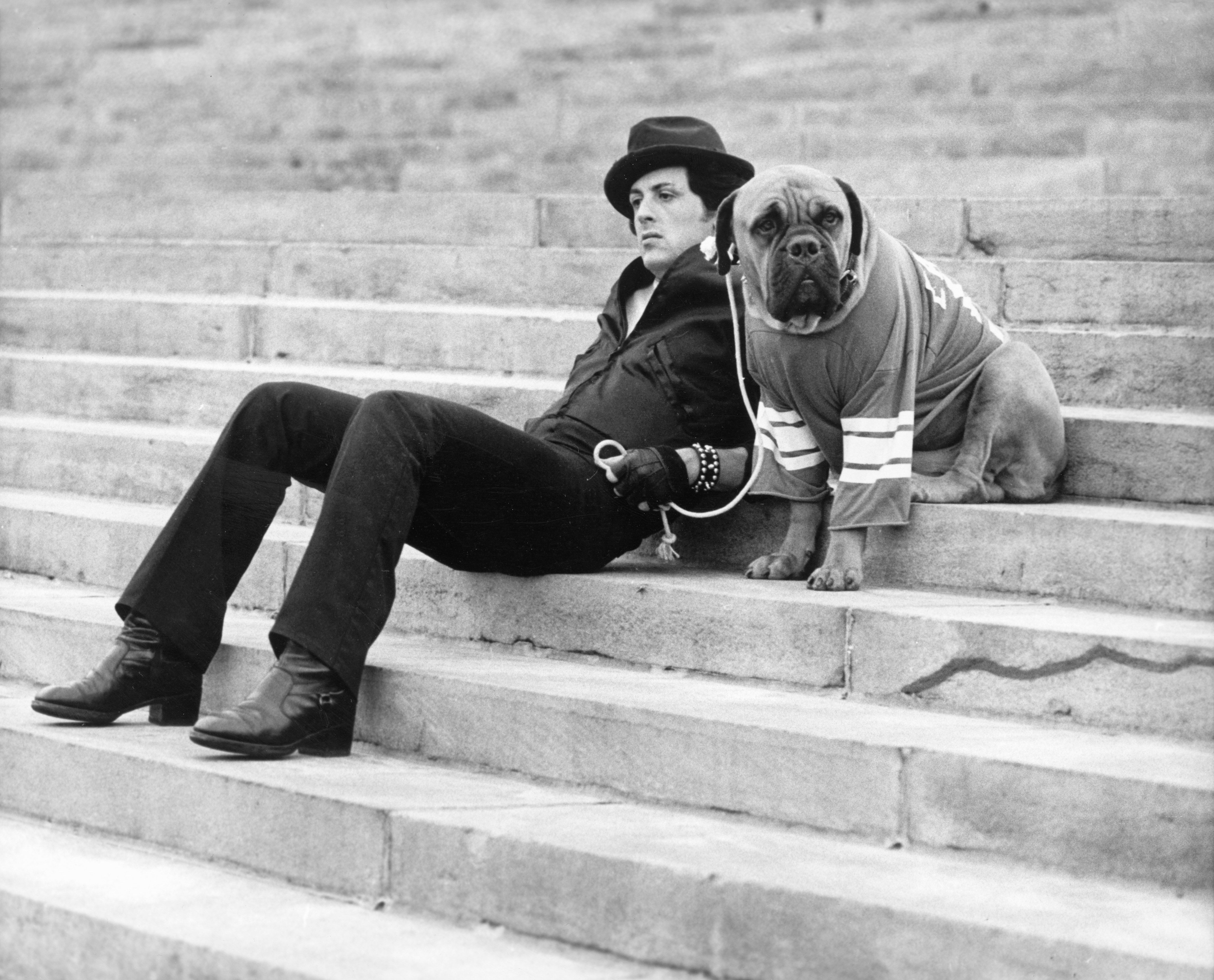"""Sylvester Stallone sits on a staircase while holding the leash of a dog in a still from the film, """"Rocky"""" in 1976. 