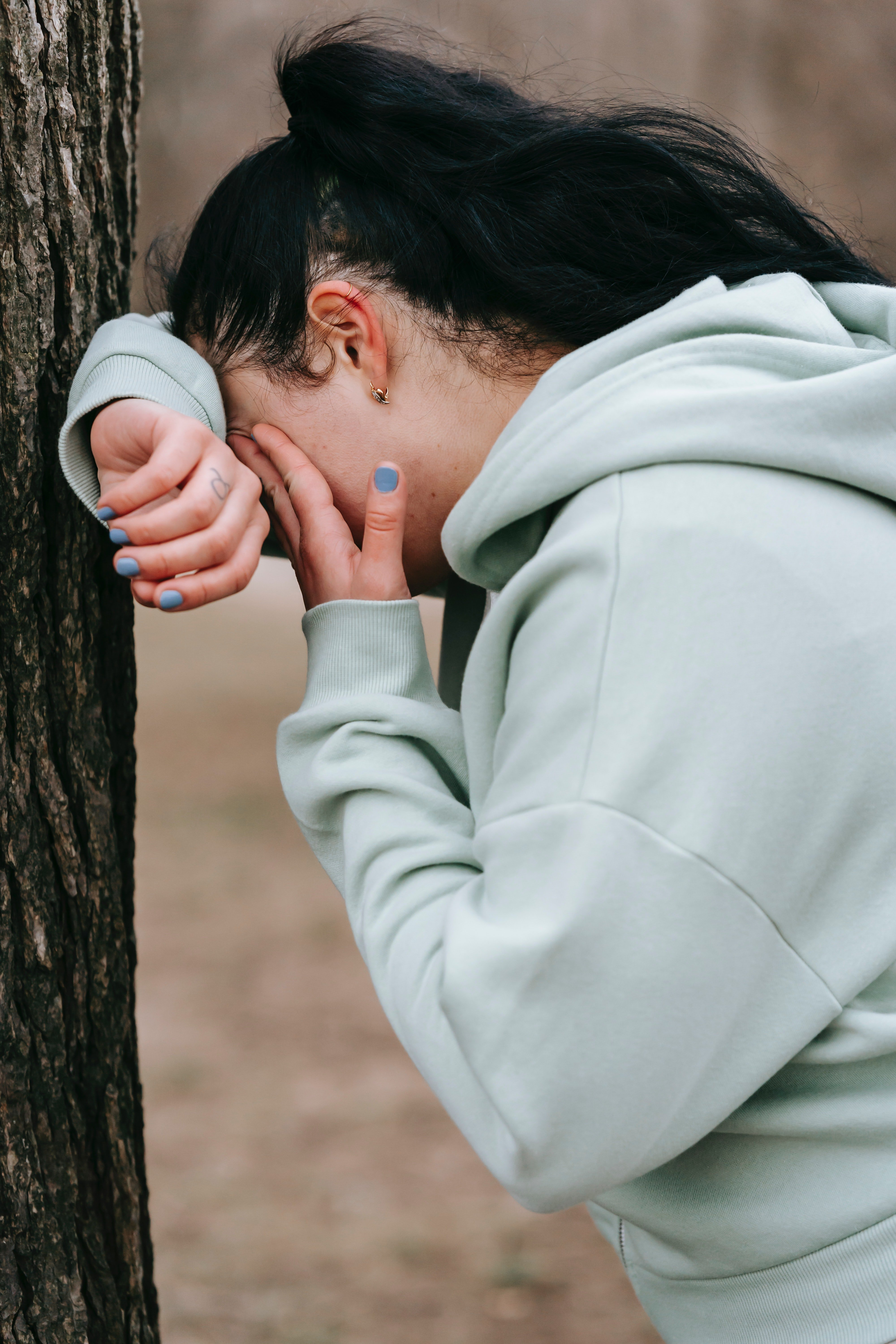 Unhappy woman leaning against a tree and crying   Photo: Pexels