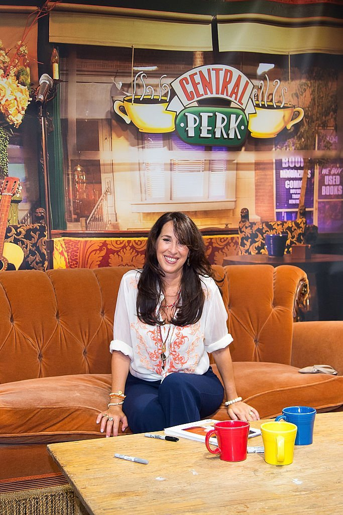 "Maggie Wheeler sits on the couch from ""Friends"" as she attends a meet and greet at Macy's Herald Square, on August 27, 2016, New York City 