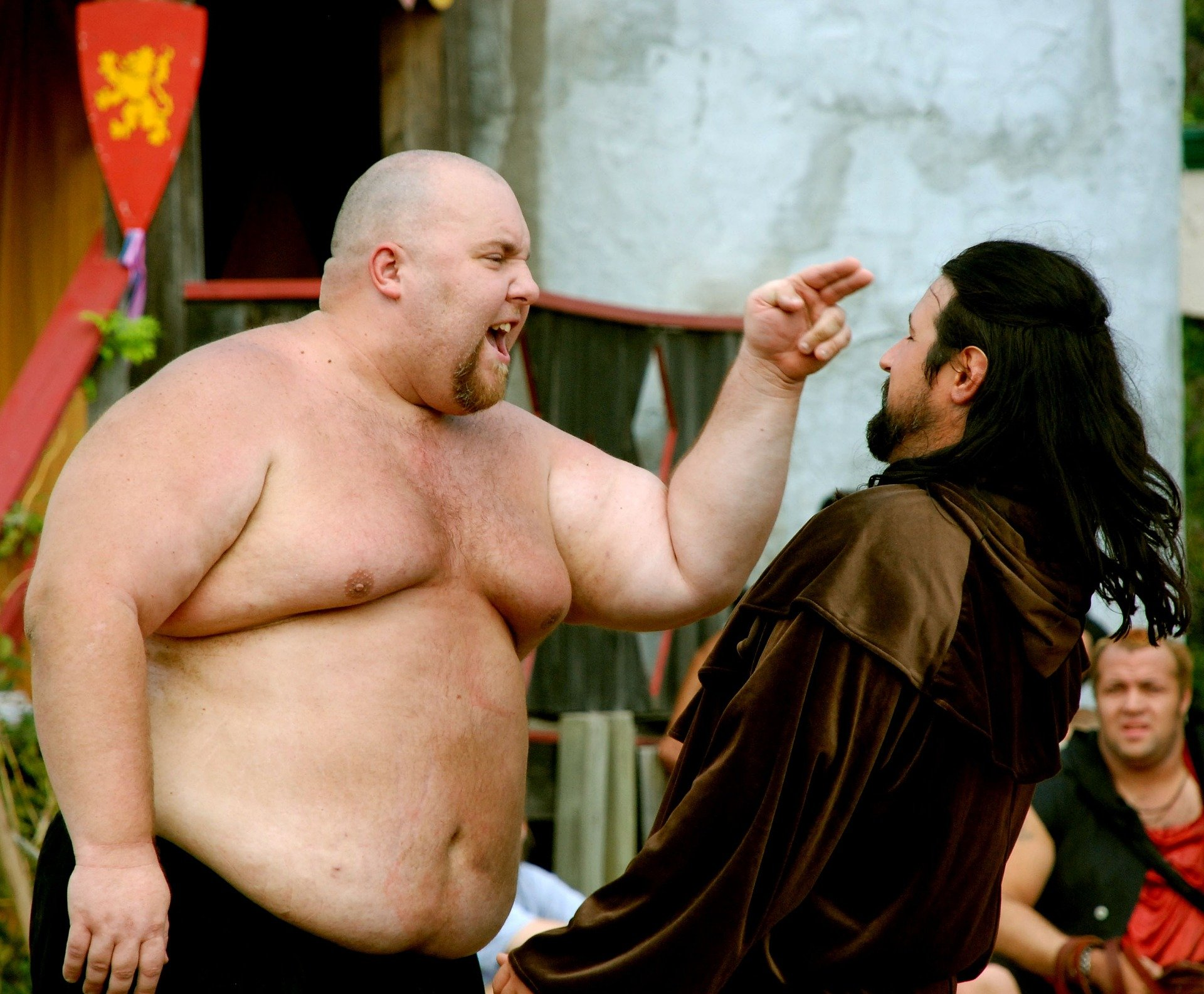 Shirtless overweight man in a confrontation with another man.   Source: Pixabay/William Adams