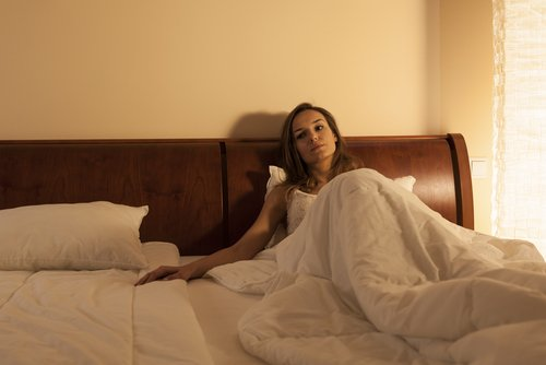 A woman wakes up alone in her bed. | Source: Shutterstock.