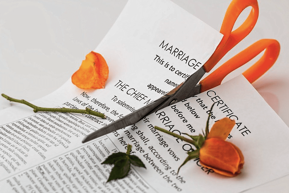 A photo of a scissors tearing through a marriage certificate | Photo: Pixabay