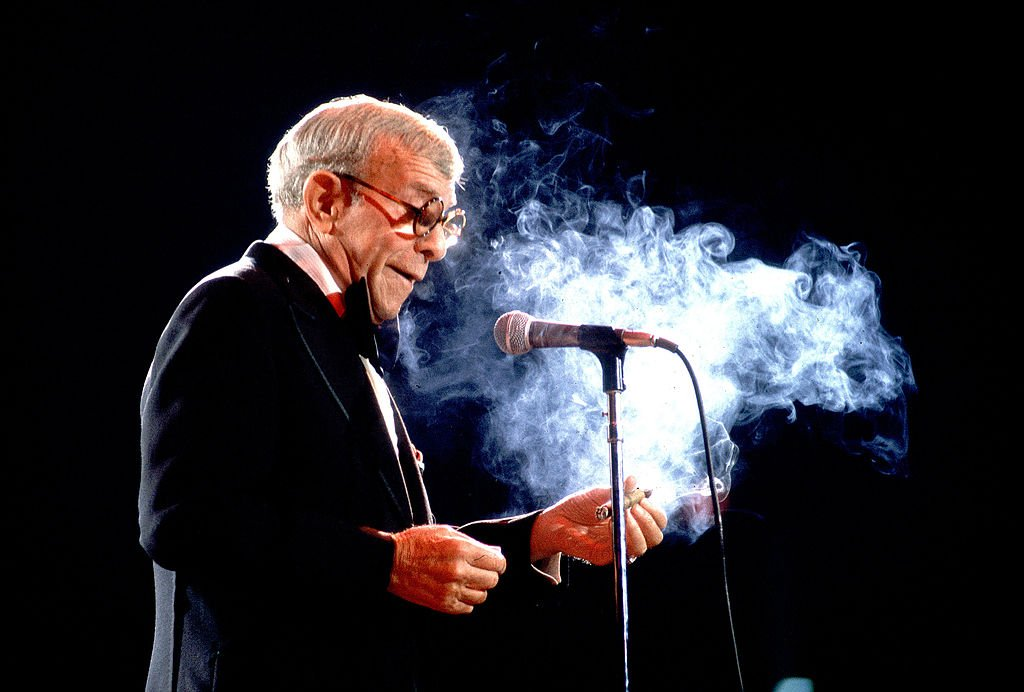 American comedian and actor George Burns (born Nathan Birnbaum, 1896 - 1996) smokes a cigar as he performs on stage, Chicago, Illinois, May 17, 1980. | Photo: Getty Images