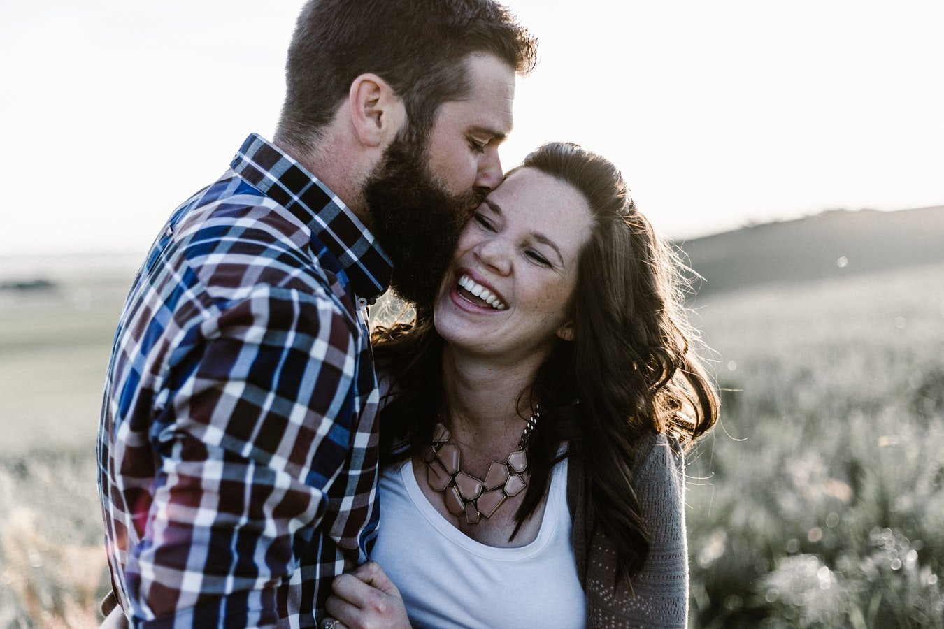 A man and woman smiling as they hold on to each other   Photo: Unsplash