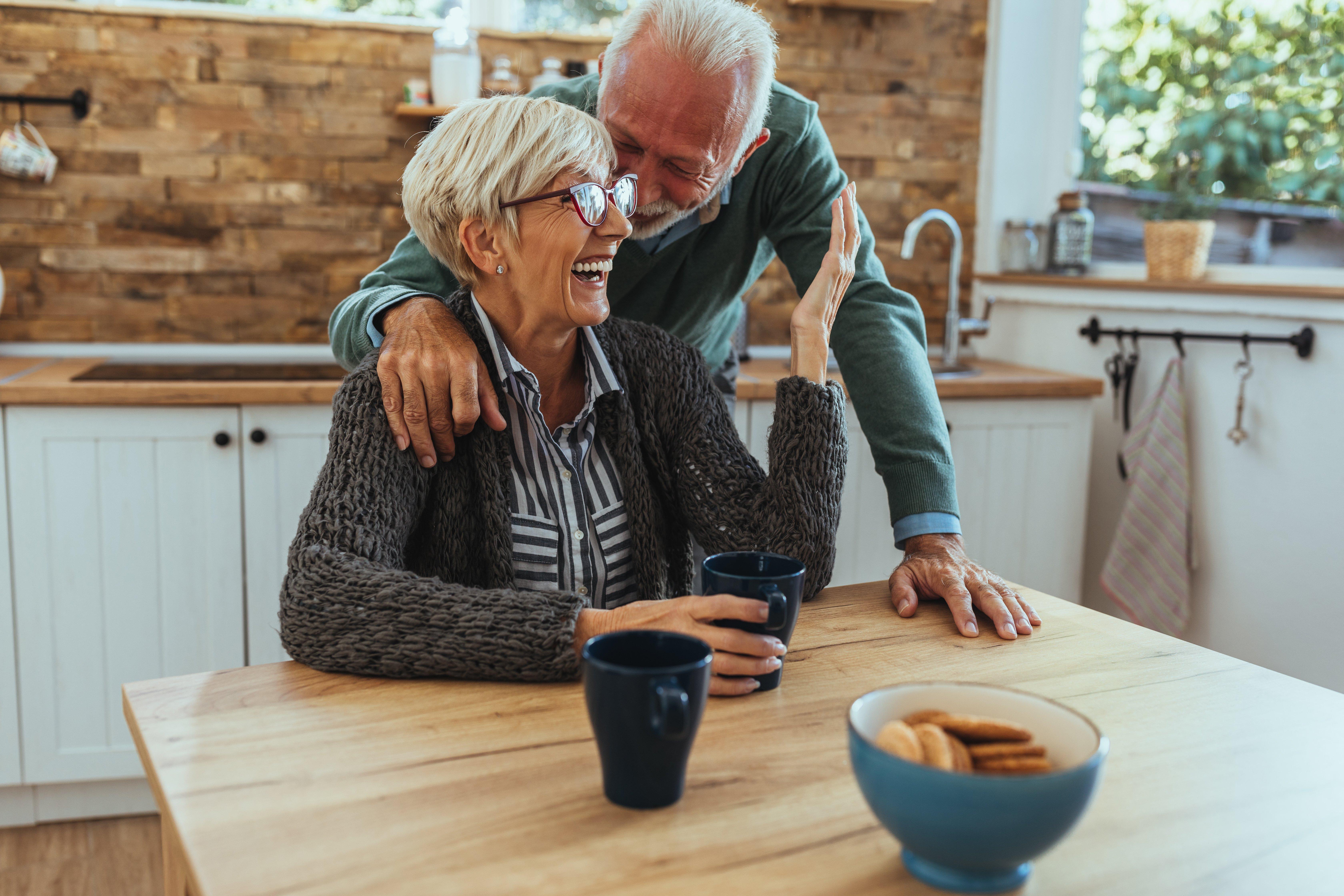Altes Paar lacht am Küchentisch   Quelle: Shutterstock