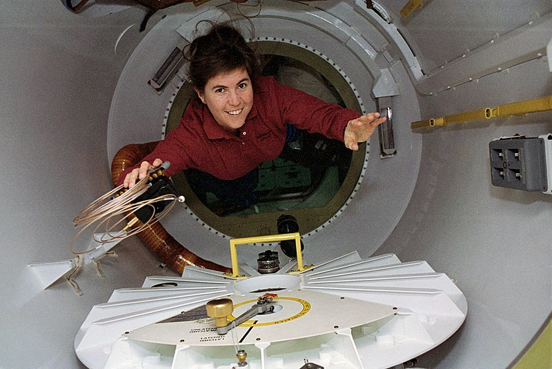 Mission Specialist Janice Voss, holding a camera, cable, & batteries, floats through the spacelab tunnel adapter on her way to the SPACEHAB module aboard Endeavour | Source: Wikimedia Commons