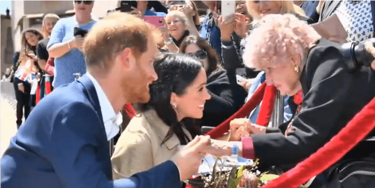 Prince Harry introducing Daphne Dunne to Meghan Markle.| Photo: YouTube/ Royal Fashion Az