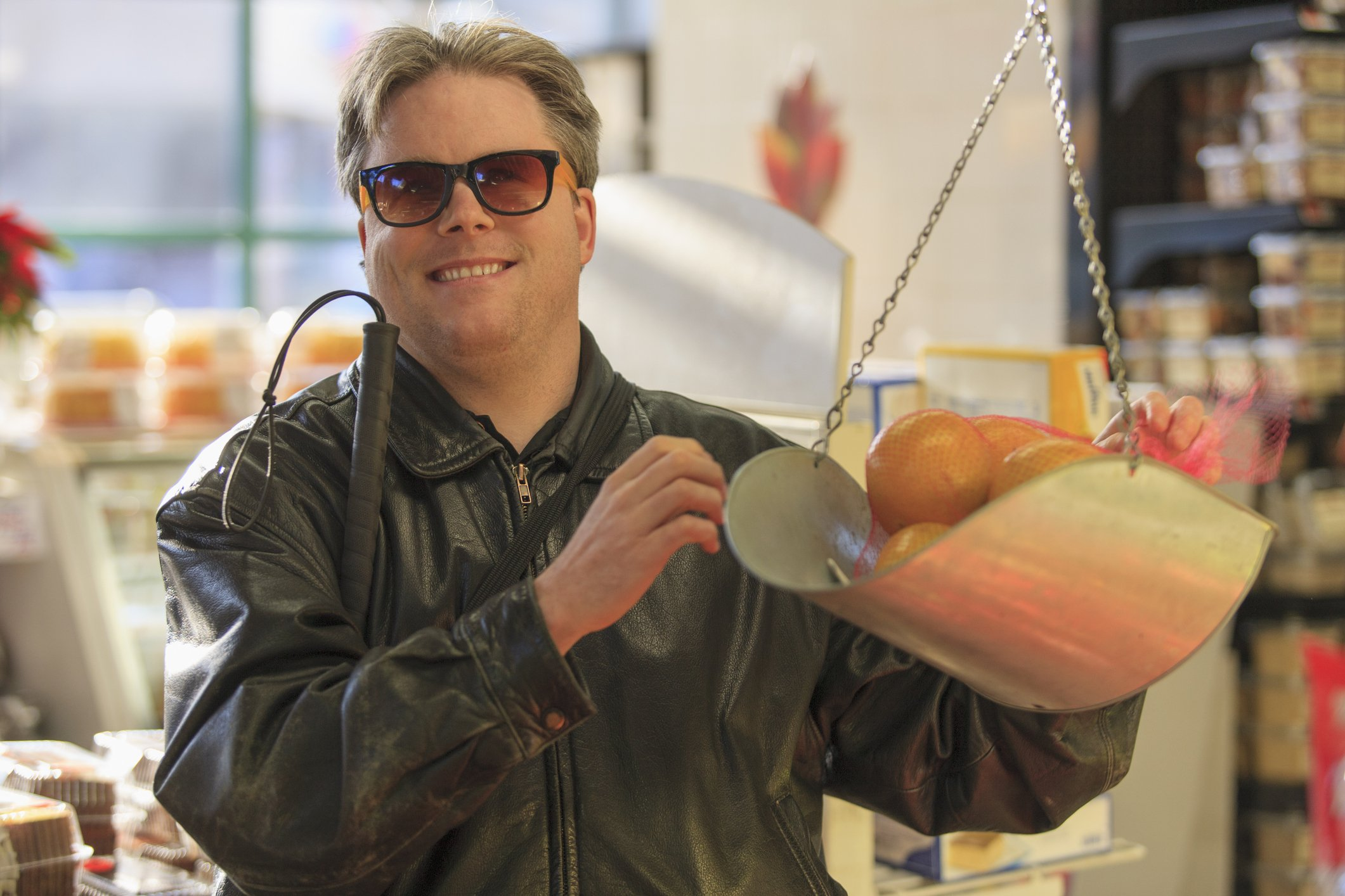 Man with congenital blindness weighing fruit at the grocery store   Photo: Getty Images