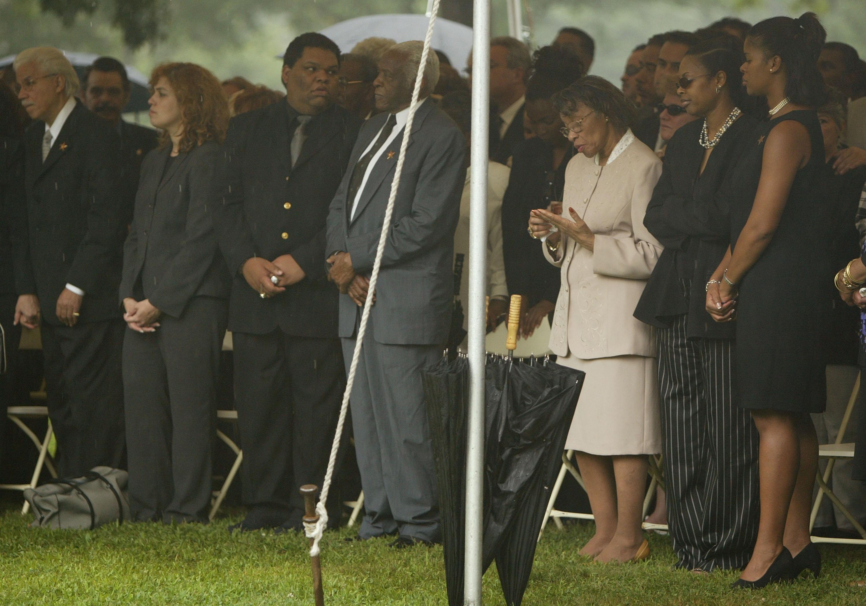 Pedro Knight, viudo de Celia Cruz, de pie junto a Gladys Bécquer (centro der.), hermana de Celia Cruz, en un tributo público en el Cementerio Woodlawn en julio de 2003 en el Bronx, Nueva York || Fuente: Getty Images