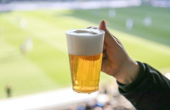 Mann hält Bier hoch | Quelle: Getty Images