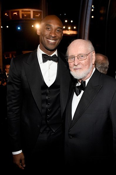 Kobe Bryant and John Williams posing in the audience during American Film Institute's 44th Life Achievement Award Gala | Photo:Getty Images