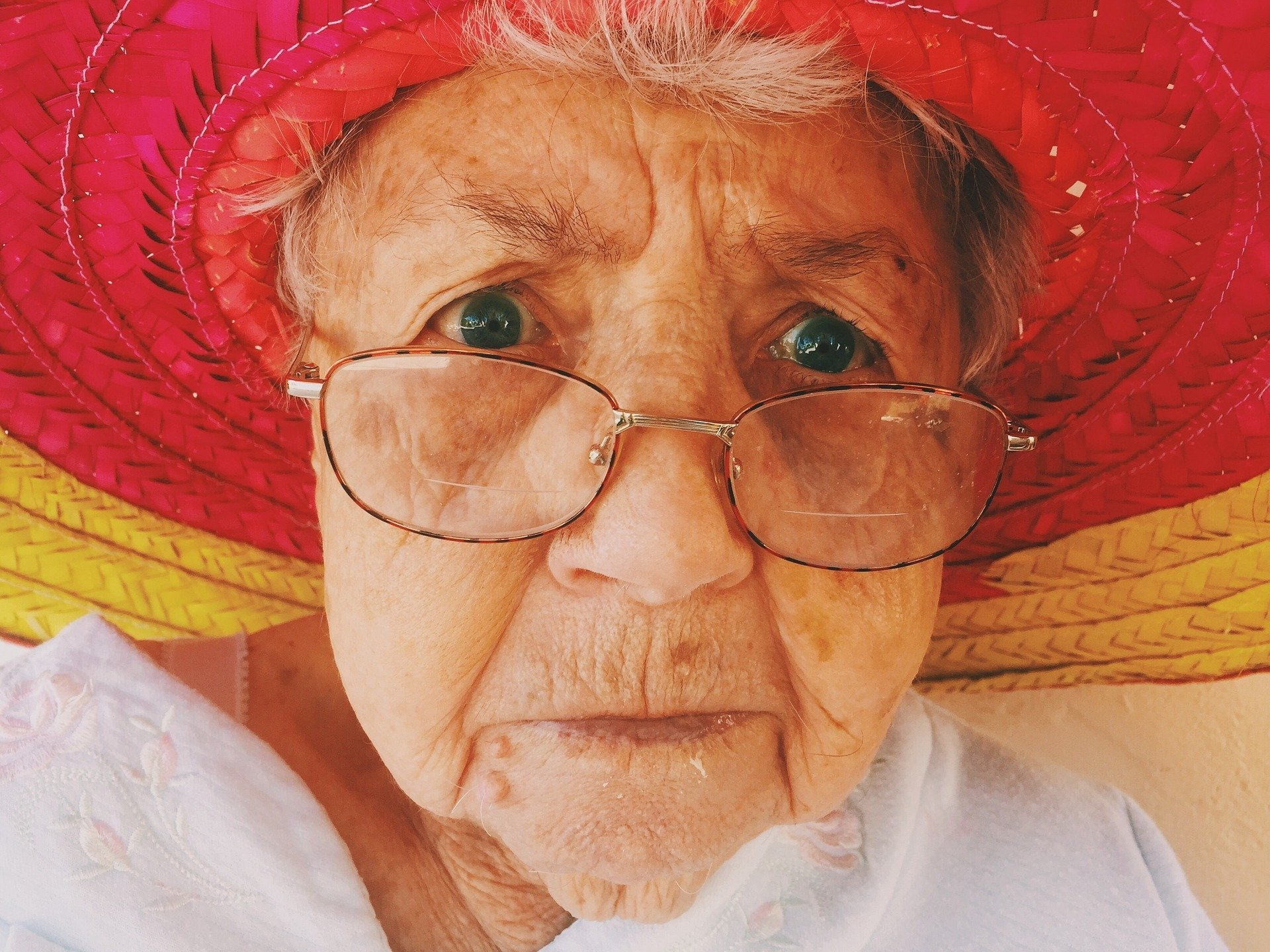 An old woman looking shocked while wearing a colorful hat and glasses. | Photo: Pixabay