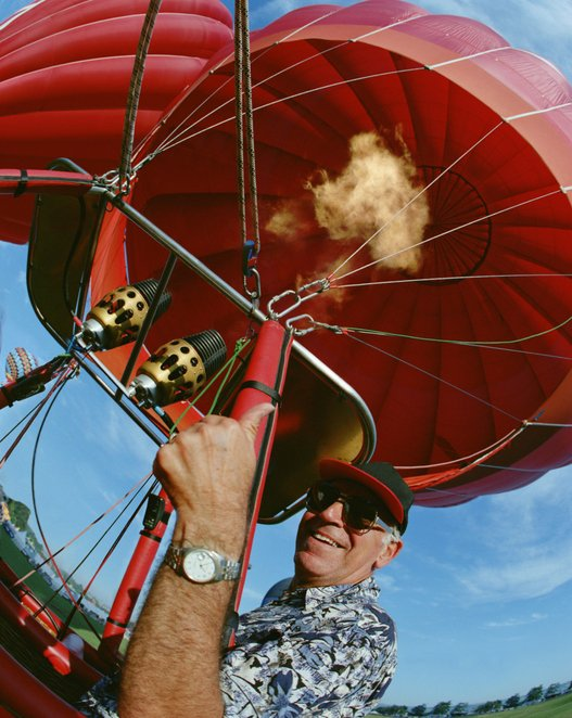 Photo of a mature man giving a thumbs up in a hot air balloon | Photo: Getty Images