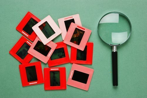 Old slides and a magnifying glass. | Photo: Shutterstock