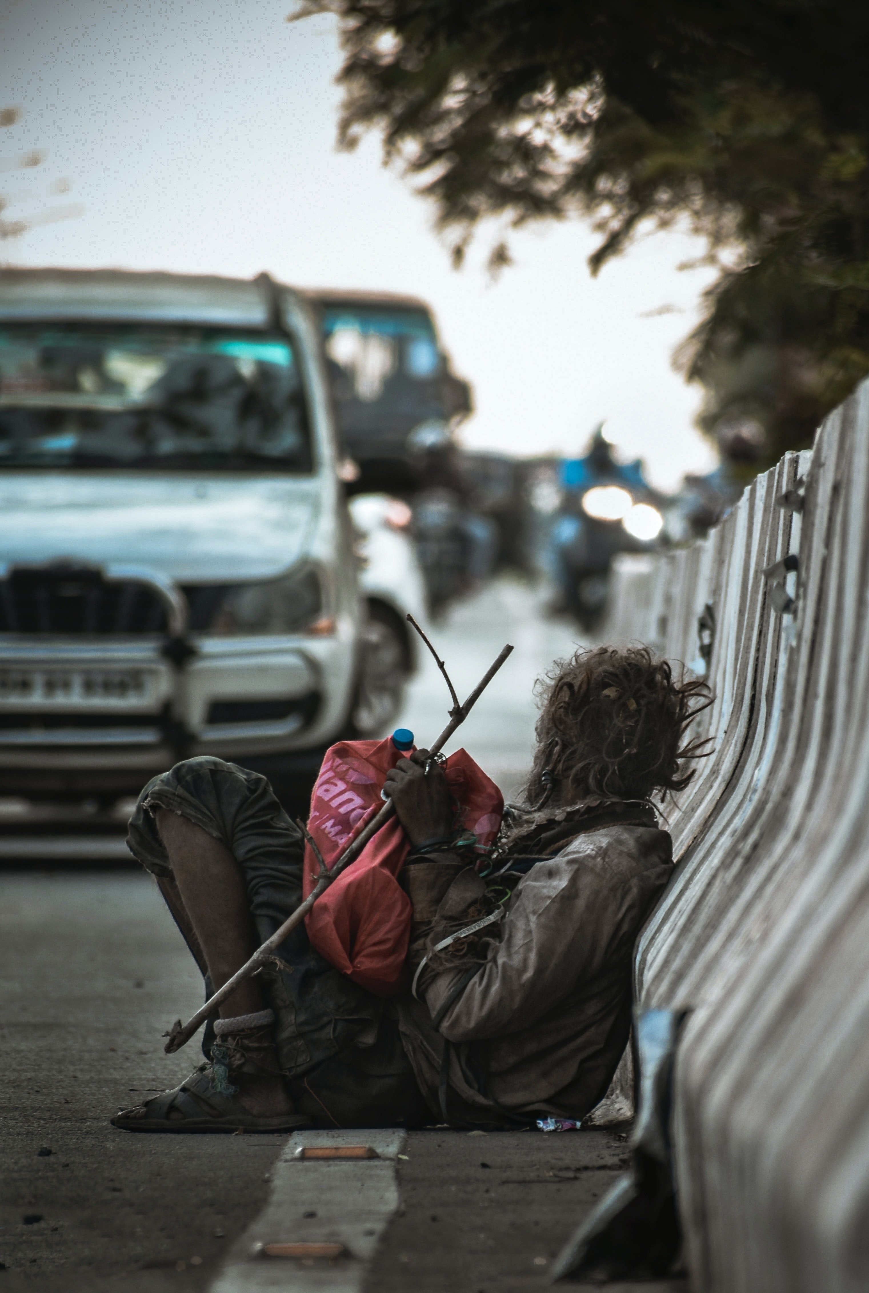 A homeless man next to the road.   Pexels/ Milan Rout