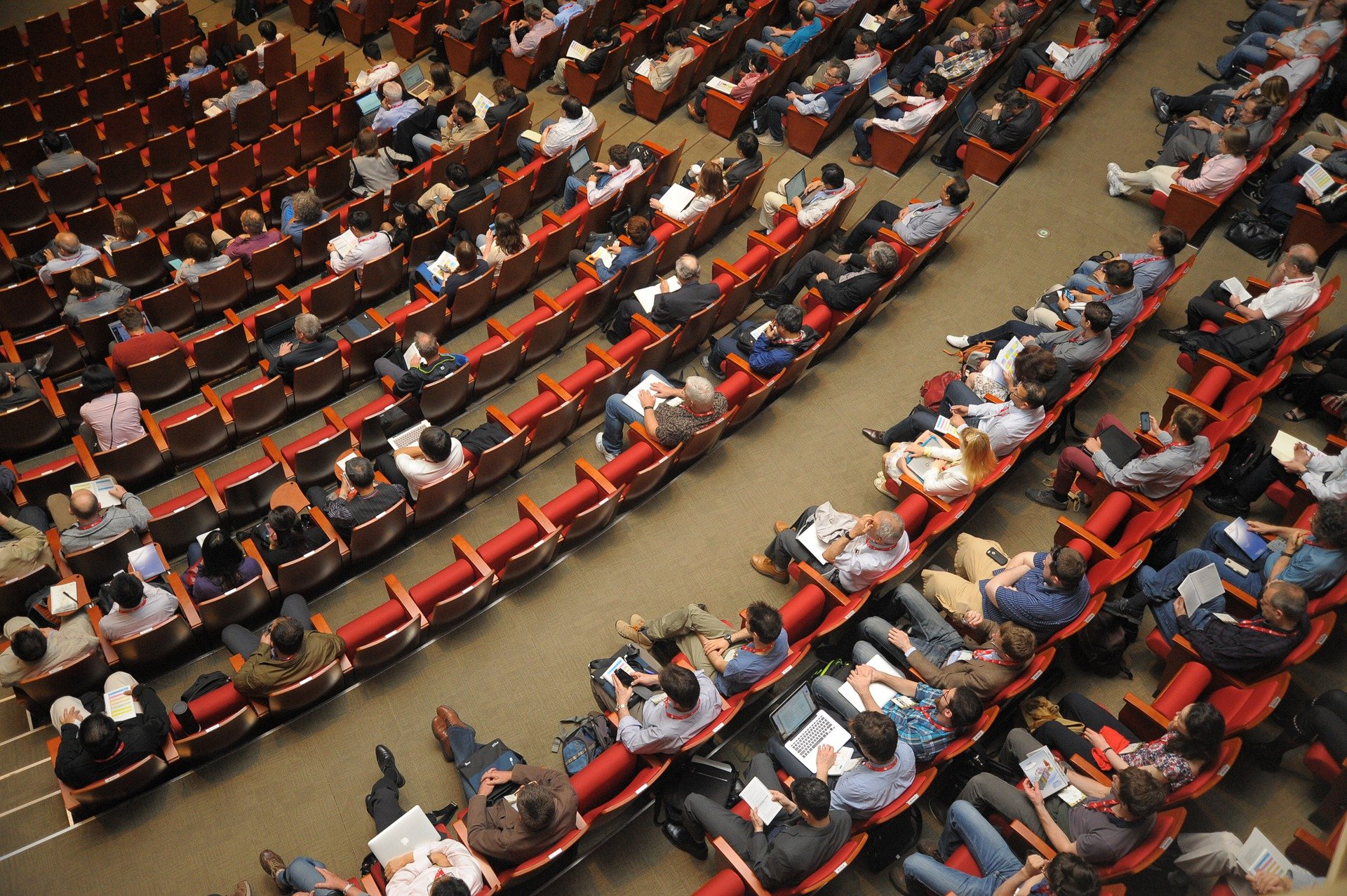 Several people sitting in an auditorium while attending a conference   Photo:Pixabay/정훈 김