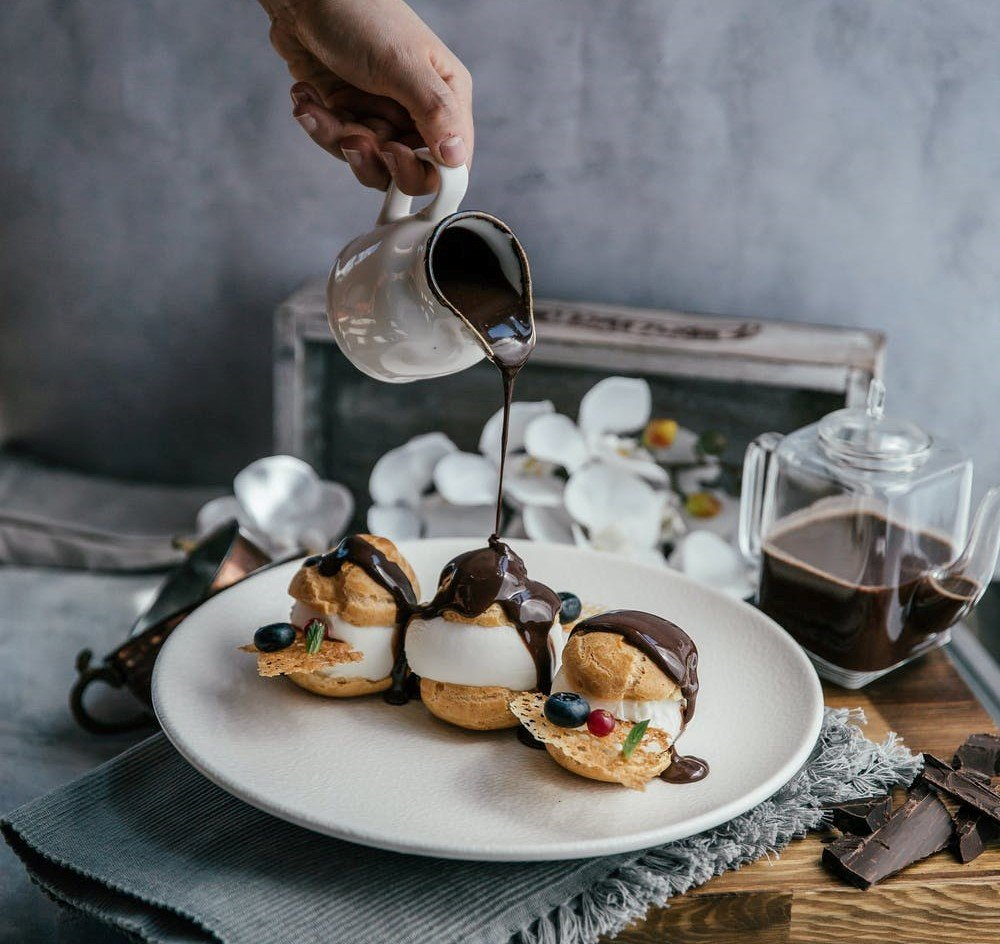 Darcy ordered profiteroles with a chocolate-rum sauce for the old woman   Source: Pexels