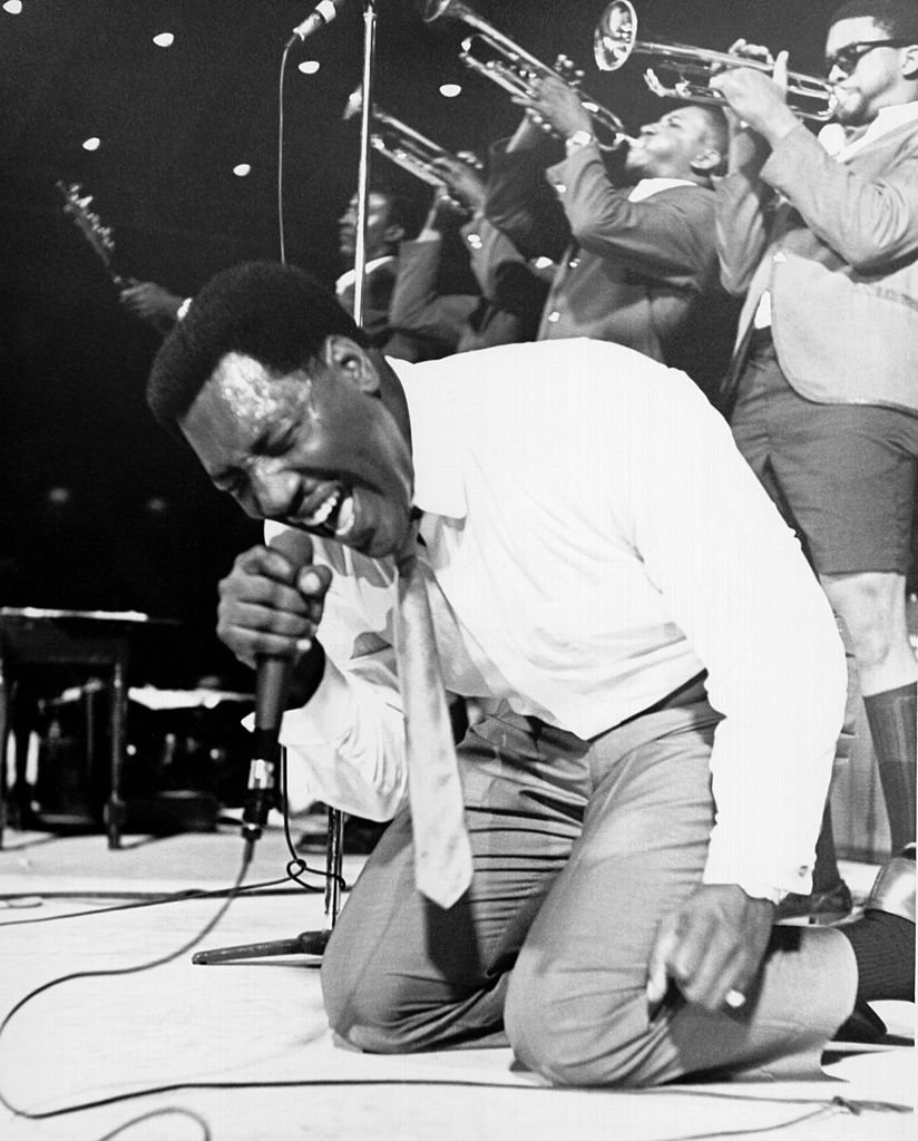 Soul singer Otis Redding passionately gets down on his knees with his horn section behind him as he performs onstage in 1967 | Photo: Getty Images