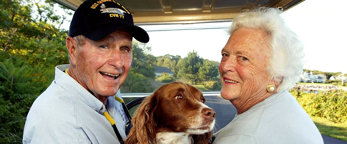 Former U.S. president George H. W. Bush and wife, Barbara Bush, in the back of a golf cart with their dog Millie at Walker's Point on August 25, 2004 | Photo: Getty Images