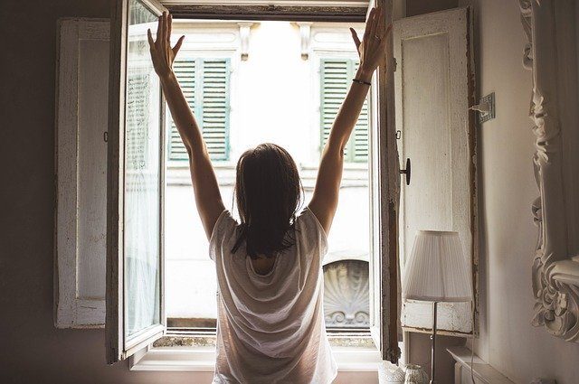 Woman looks out window with outstretched hands | Photo: Pixabay