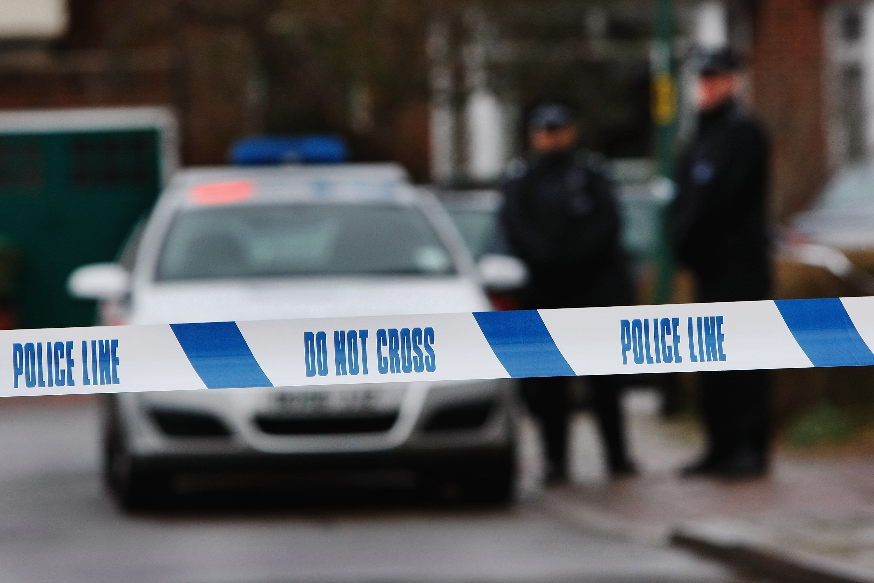 Police officers in a crime scene blocked by tape. | Source: Getty Images