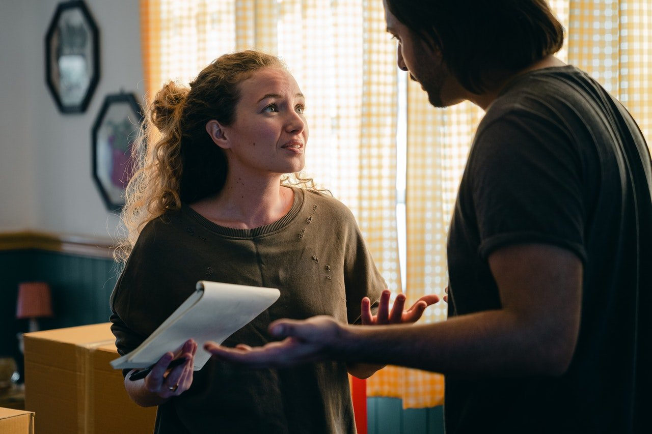 Woman holding a notepad while arguing with a man   Source: Pexels