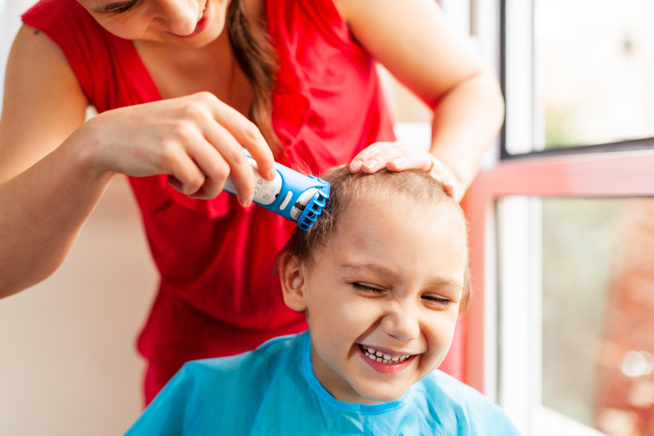 Mother trimming toddlers hair  | Photo: Getty Images