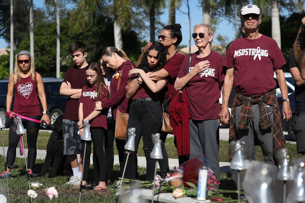 People pause for a moment of silence at 10:17 am on Thursday, February 14, 2019 near Marjory Stoneman Douglas High School as they remember those lost during the Parkland Mass Shooting. | Photo: Getty Images